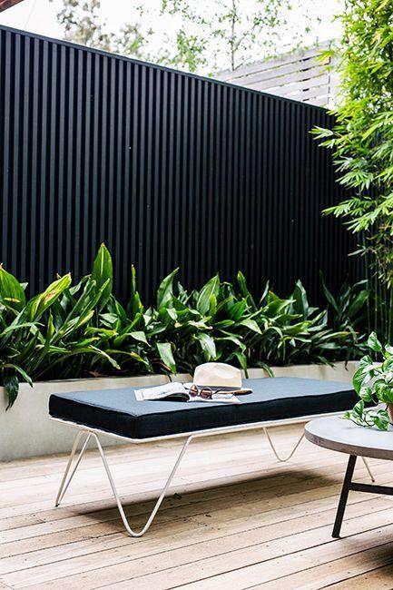 Betonnen plantenbak tegen zwarte schuttingen