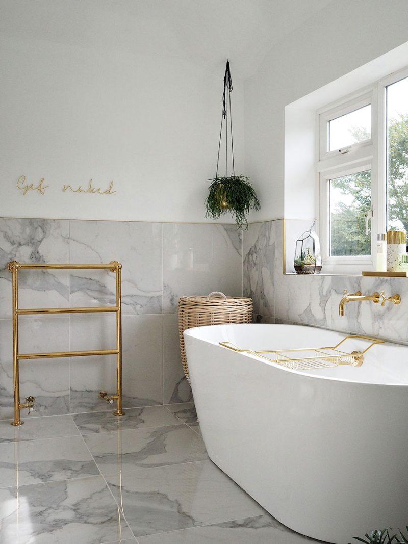 De luxe chique badkamer van Olivia waar marmeren tegels gecombineerd zijn met gouden accenten.