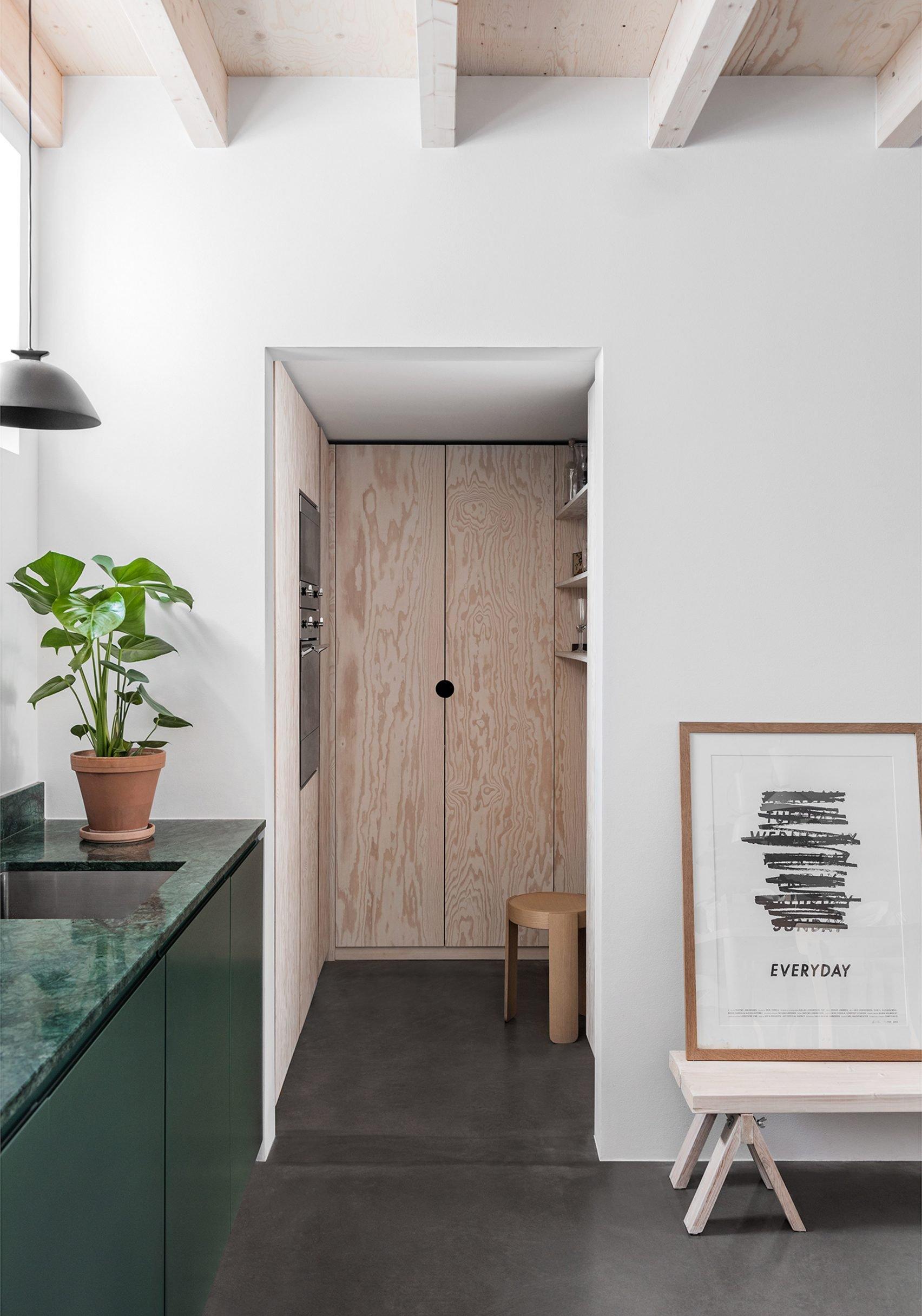 Deze mooie groene keuken loopt aan de andere kant van de deuropening door