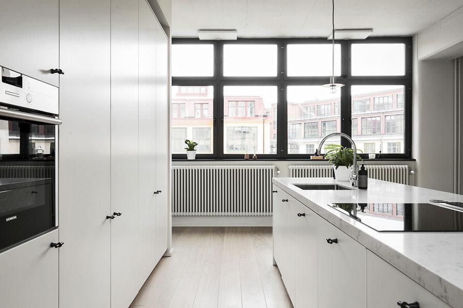 Een moderne witte keuken met een dik wit marmeren keukenblad. Klik hier voor meer foto's.