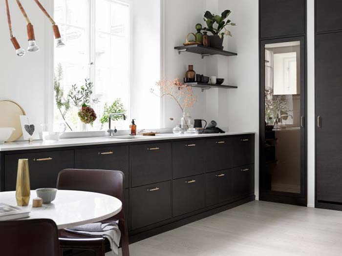 Een mooi contrast tussen de donkere keukenkasten en het witte marmeren keukenblad. Klik hier voor meer foto's.