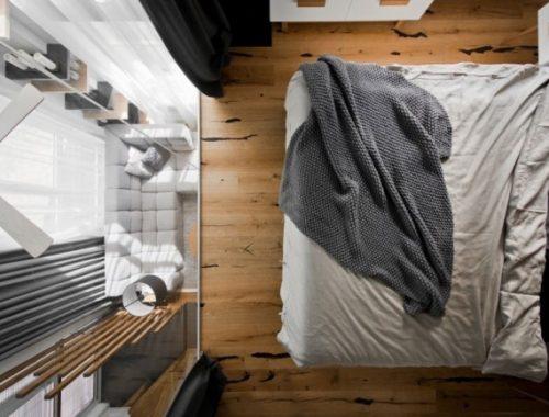 Glazen wand in slaapkamer biedt uitzicht op woonkamer