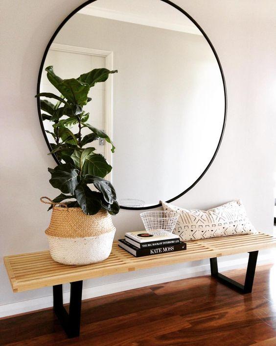 Grote ronde spiegel aan de muur boven een bankje