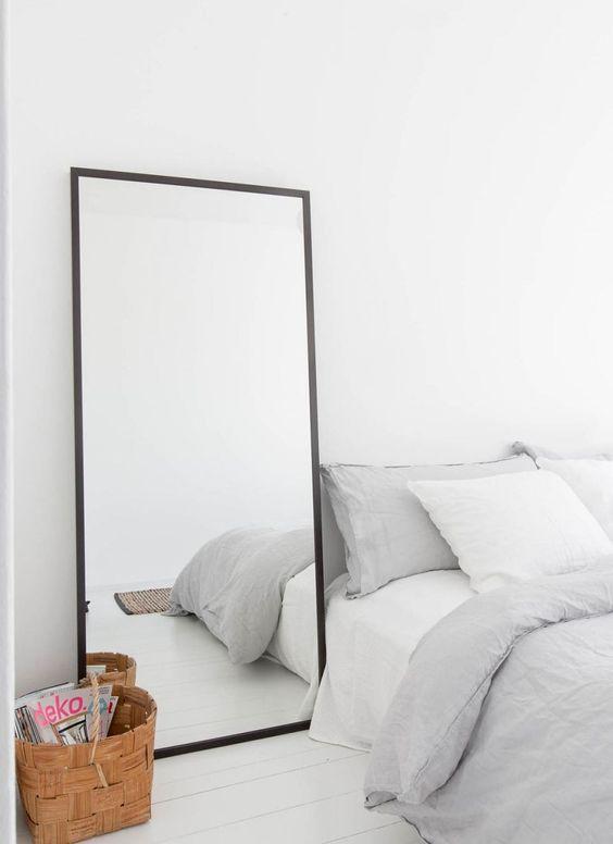 Grote spiegel op de vloer naast het bed