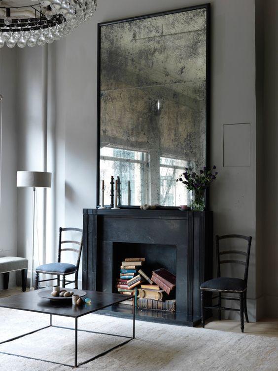 Prachtige grote spiegel op een klassieke zwarte schouw.