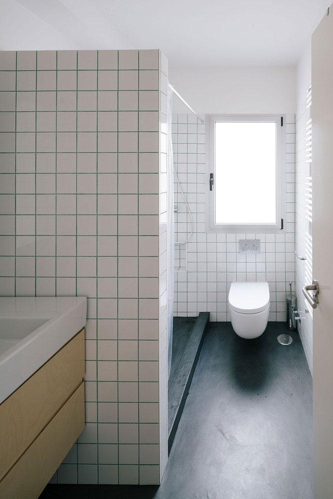 In dit toilet zijn de witte wandtegels gecombineerd met felroze voegen!