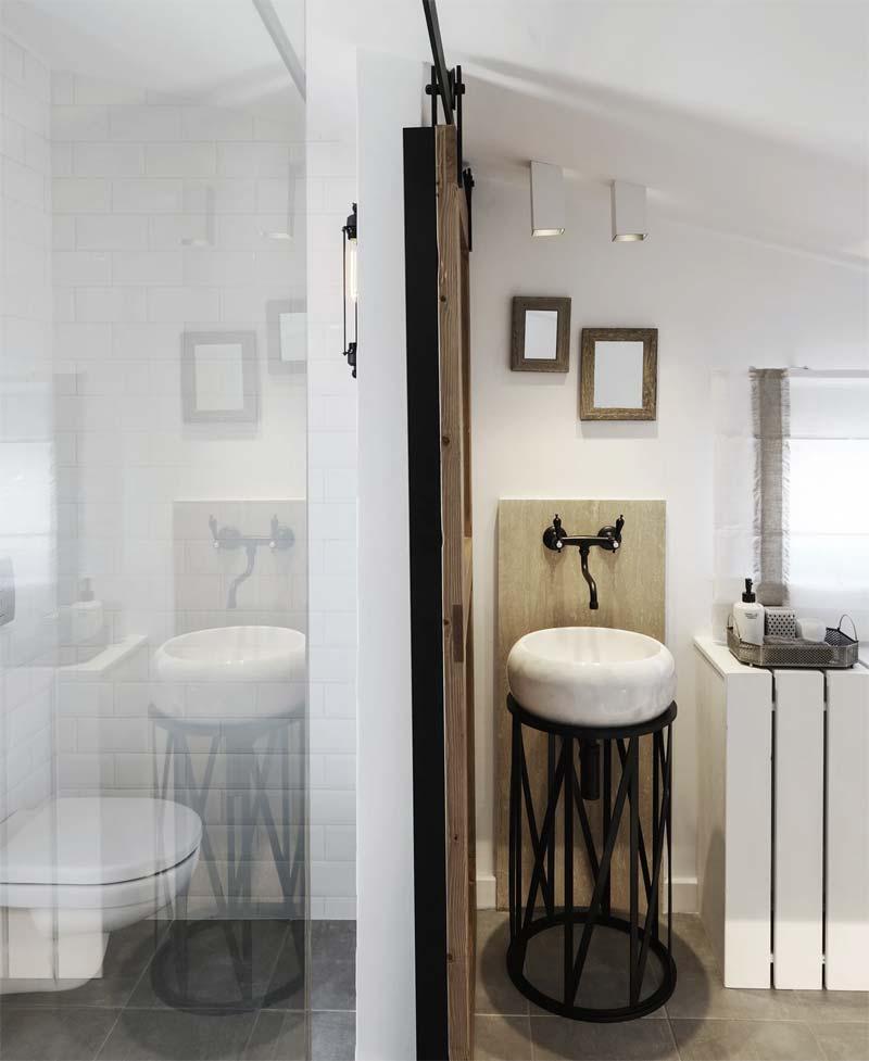 Architectenbureau Ark4lab heeft voor deze open badkamer gekozen voor een klassieke zwarte wastafelkraan, die super mooi staat bij de houten boerderij schuifdeur. Klik hier om meer foto's te bekijken.