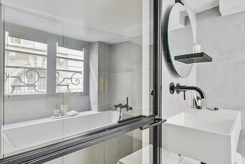 In deze kleine badkamer is er gekozen voor meerdere zwarte details, met een stoere stalen deur, zwarte wandplank aan de ronde spiegel, zwarte stopcontacten en een zwarte wastafelkraan. Klik hier om meer foto's te bekijken.