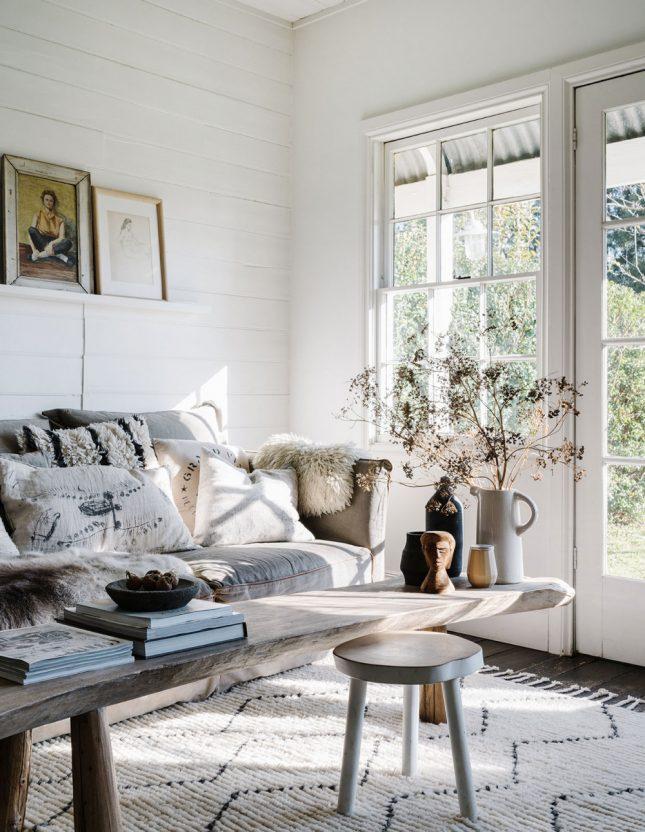 Dit is de super mooie en vooral erg knusse zithoek van Lynda Gardener. Er is veel textuur gecreeerd met een mooi vloerkleed en heel veel kussens op de stoffen bank. De grote rustieke bank als salontafel is ook een goed idee.