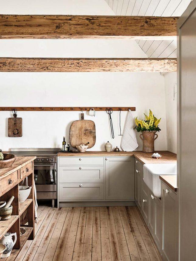Mooie landelijke keuken van Nordiska Kök, gecombineerd met een vintage houten werktafel in het midden van de keuken.