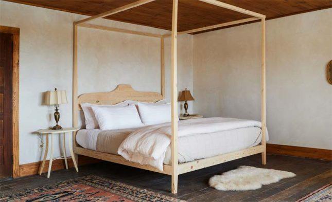 Ziet deze slaapkamer in moderne landelijke stijl er niet super mooi, knus en dromerig uit? Jersey Ice Cream Co heeft een kamer gecreëerd die bescheiden en tegelijkertijd luxueus is, onder andere dankzij een groot houten hemelbed, een vintage vloerkleed en een zacht schapenvachtje op de vloer.