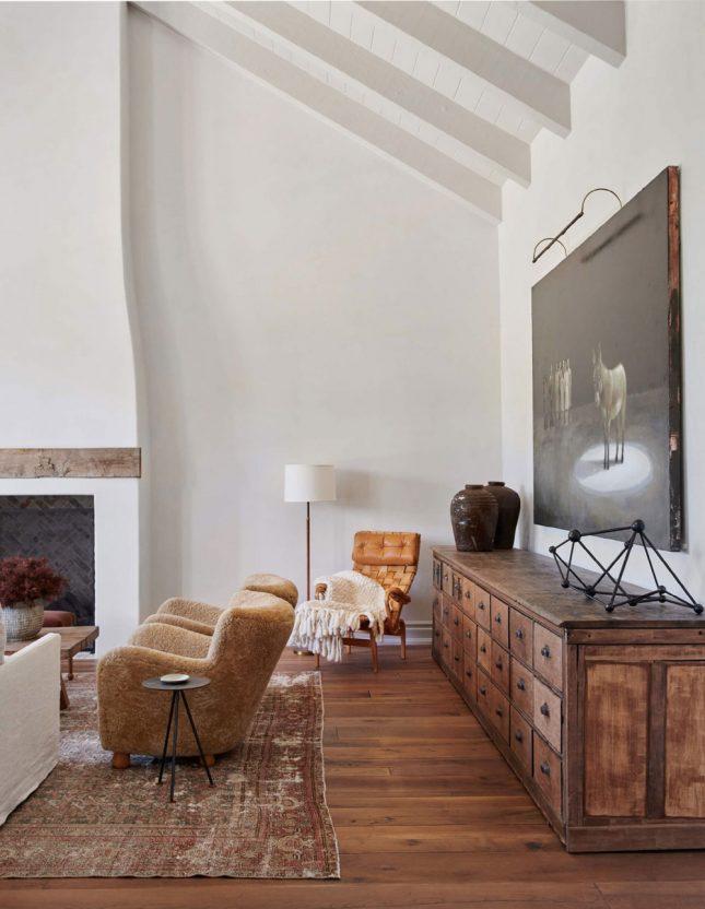 In deze landelijke woonkamer worden natuurlijke texturen gecombineerd voor een harmonieuze look. Houten vloer, mooie gestoffeerde fauteuils, een lichte linnen bank, een vintage vloerkleed en een grote houten buffetkast.