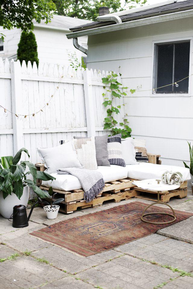 Leuke tuin met een loungebank van houten paletten