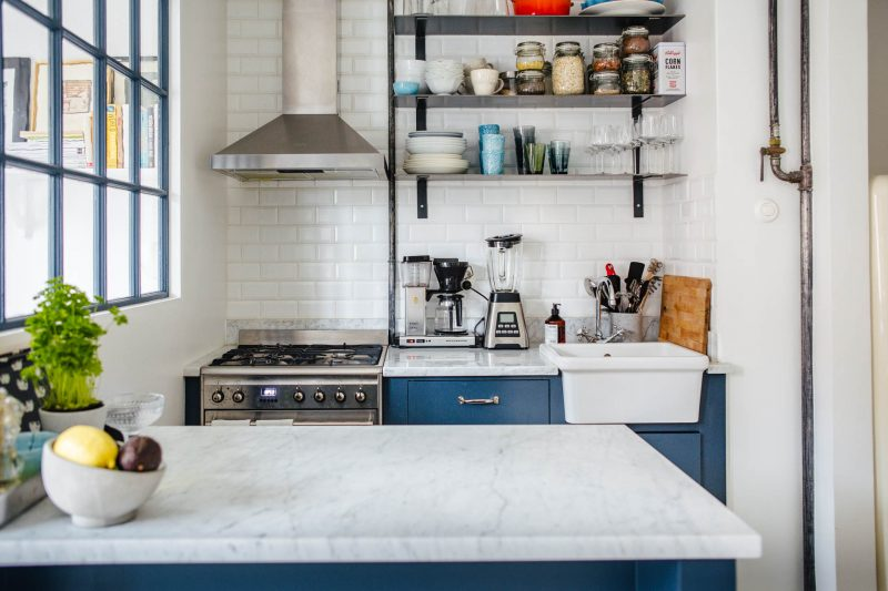 Deze kleine keuken met schiereiland combineert blauwe kasten met een wit marmer keukenblad. Klik hier voor meer foto's.
