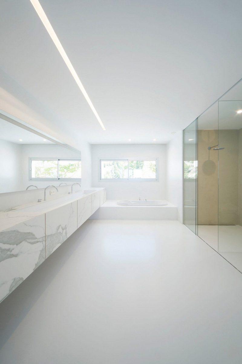 In deze moderne luxe badkamer loopt de marmeren badkamermeubel over de hele breedte van de muur.