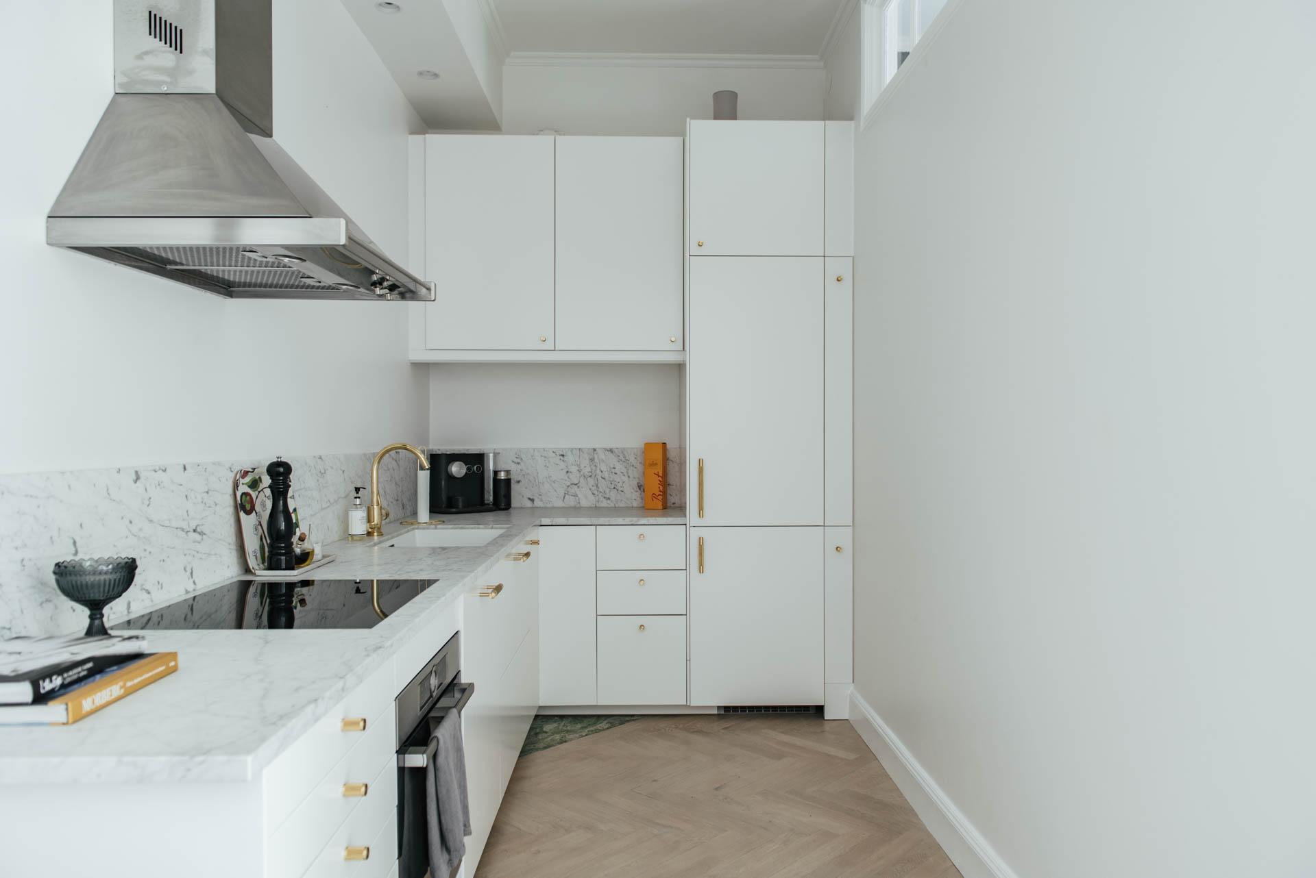 Deze moderne keuken laat zien dat witte keuken, gouden deurgrepen en een wit marmeren keukenblad een mooie combinatie blijft. Klik hier voor meer foto's.