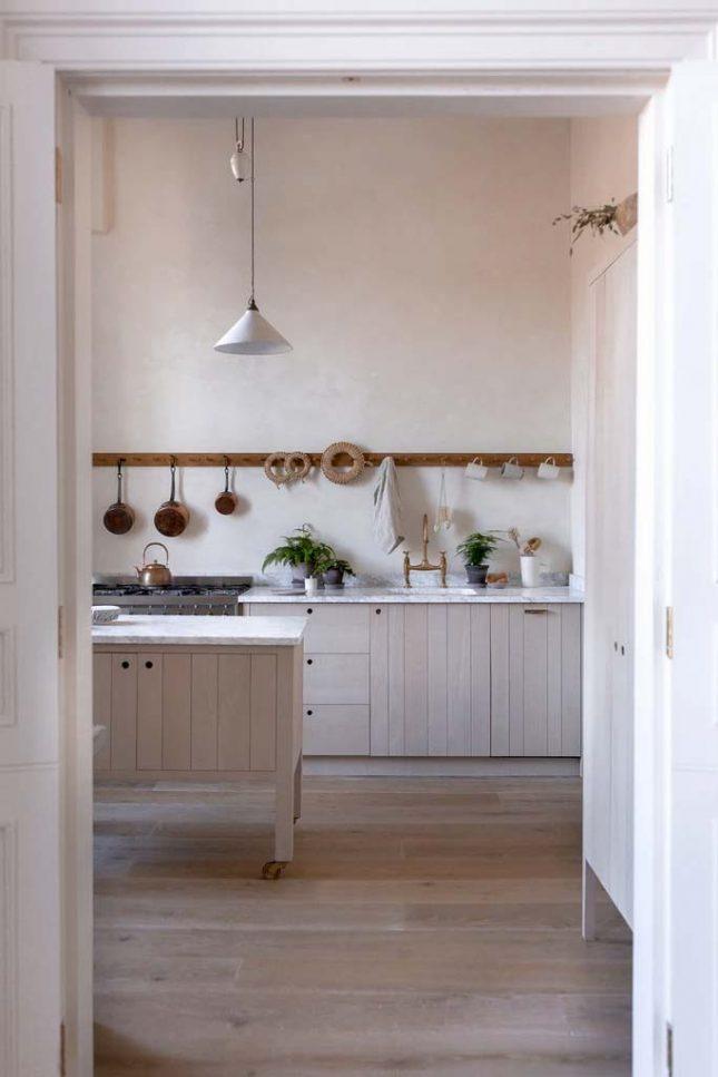 Natuurlijke houten keuken met gipsen muren, marmeren werkblad, peg rail voor pannen en keukengerei, en keukeneiland op wielen.