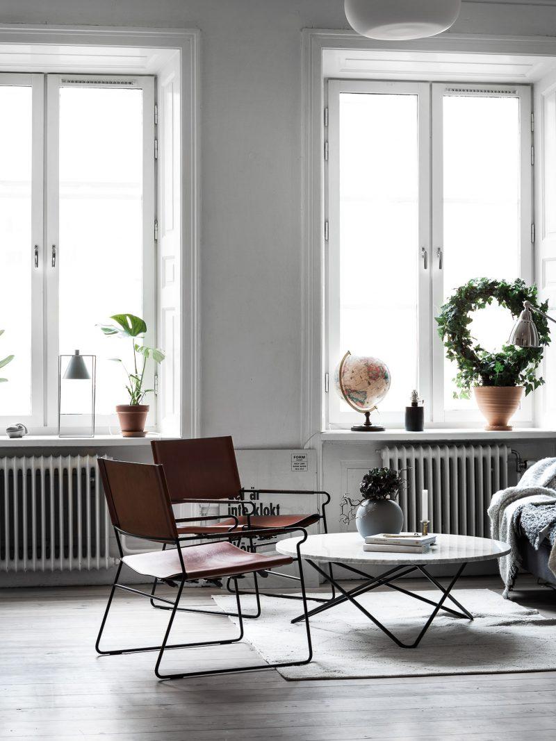 De ronde marmeren salontafel staat super mooi bij de bruine leren stoelen in deze woonkamer. Klik