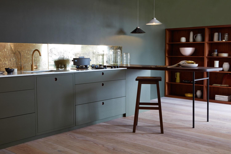 In deze super stijlvolle keuken is er gekozen voor mosgroene keukenkasten, een gouden keuken achterwand en een wit marmeren keukenblad. Klik hier voor meer foto's.