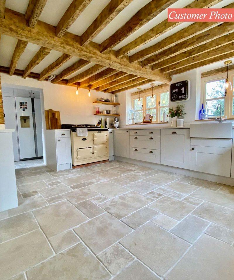 De prachtige travertin tegels passen perfect in deze landelijke rustieke keuken.