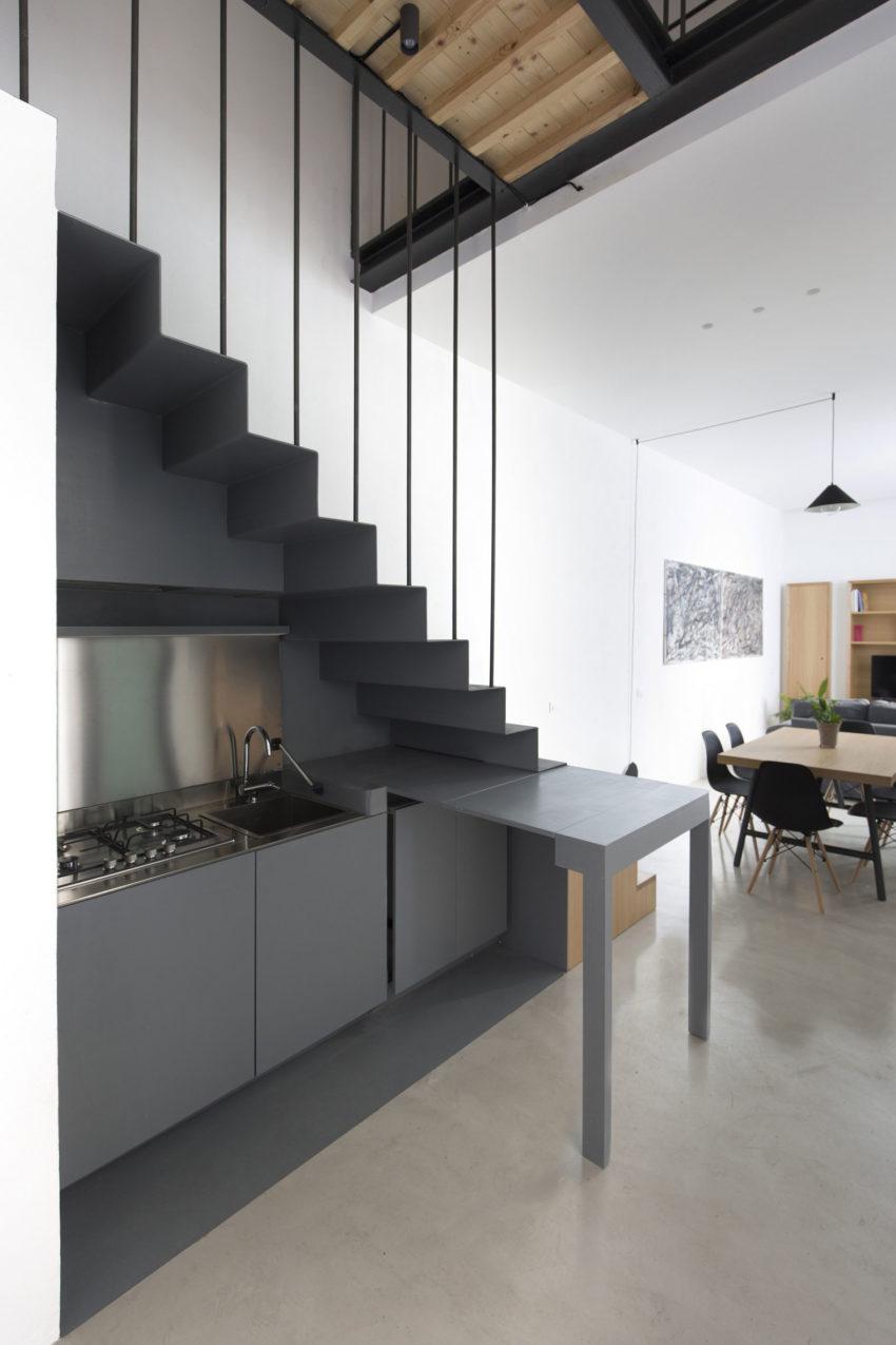 Onder deze stoere trap is een keuken ingericht!