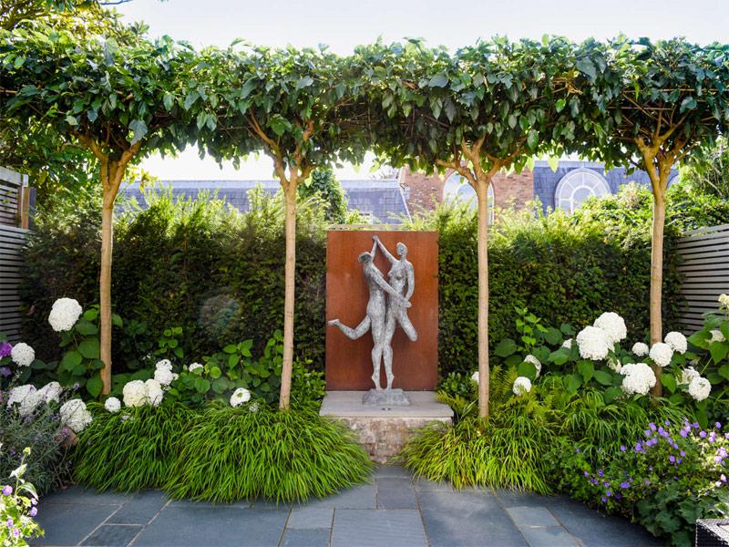In deze romantische tuin heeft Garden Club London gekozen voor een mooi groot standbeeld tussen alle mooie planten, bomen en bloemen.