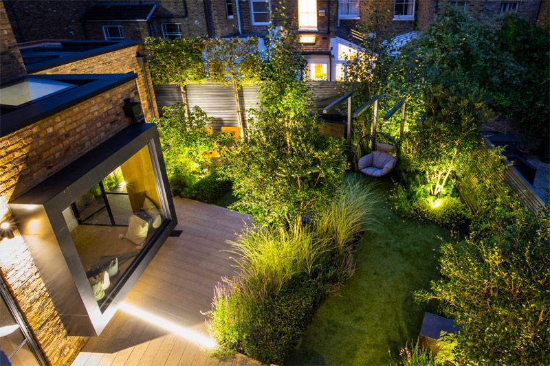 Deze moderne romantische tuin, ontworpen door Garden Club London, is prachtig verlicht. Het zithoekje in de hoek is ook een super leuk ideen.