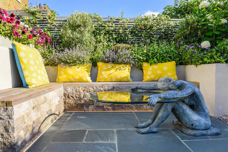 Het Chadwick project van Garden Club Londen bevat een romantische zithoek met een vaste bank en begroeide schutting met mooie planten met bloemen.