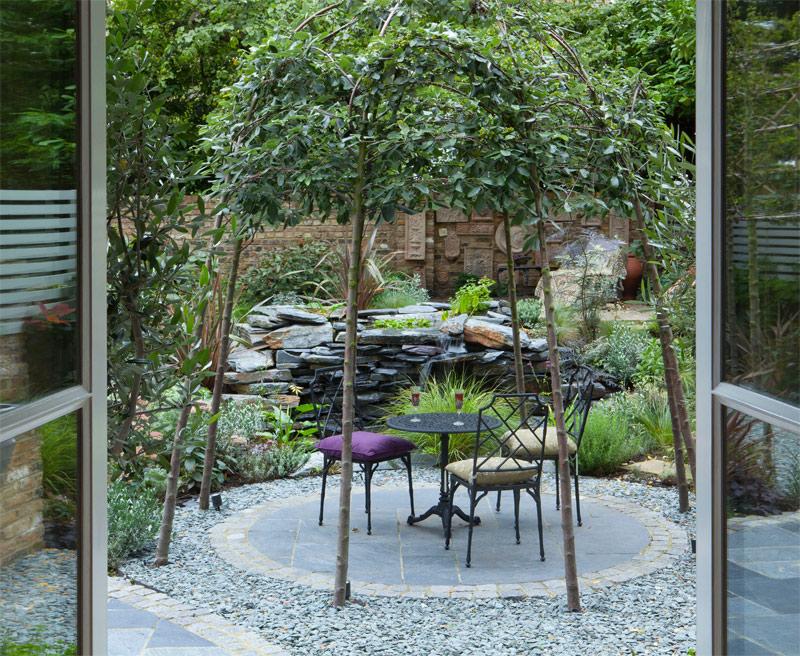 London Garden Designer heeft deze super mooie romantische tuin ontworpen met onder andere een zitplek met bistrot tafelset onder een groene prieel