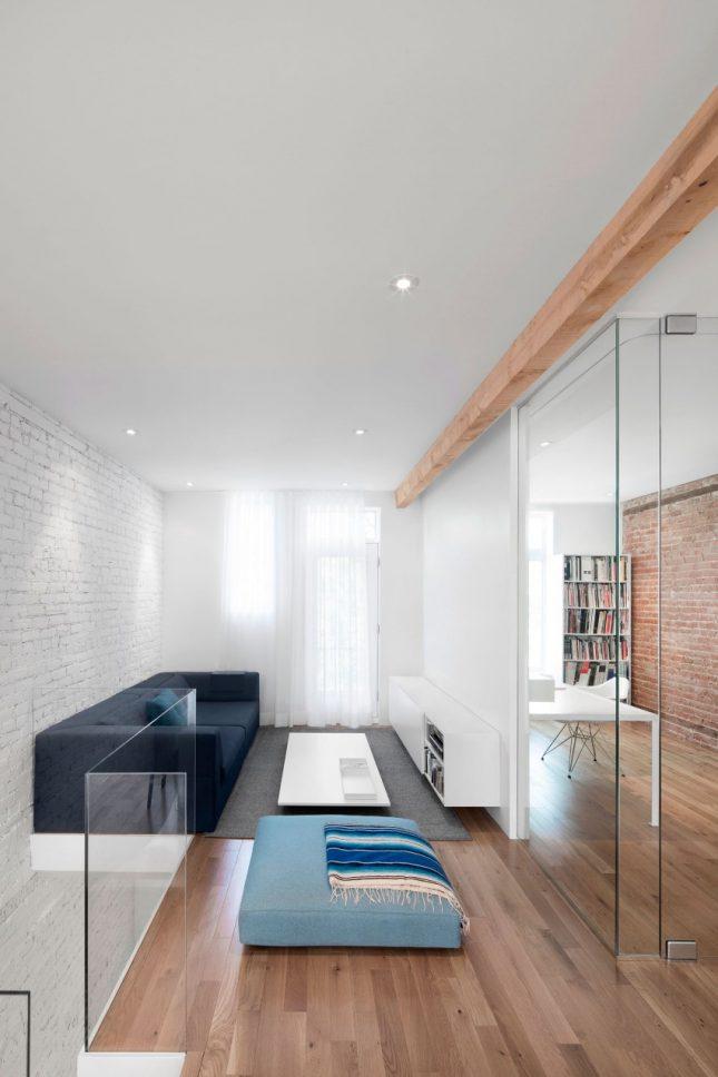 Ruimtelijke smalle woonkamer door glazen wand