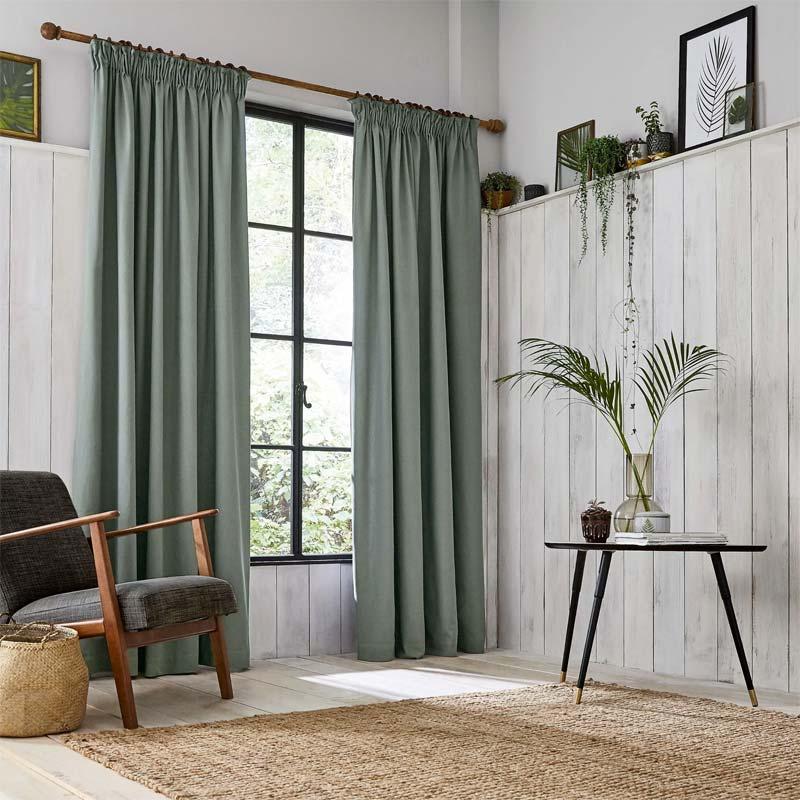 De Sage green gordijnen in deze kamer vallen mooi op, tegen de lichte achtergrond en de zwarte kozijnen.