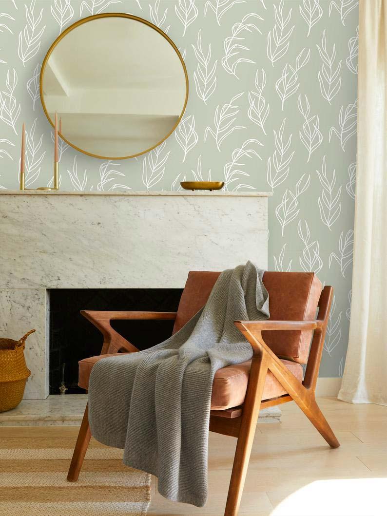 In deze mooie zithoek met open haard is de muur behangen met prachtig Sage green behang met een wit patroon van bladeren.