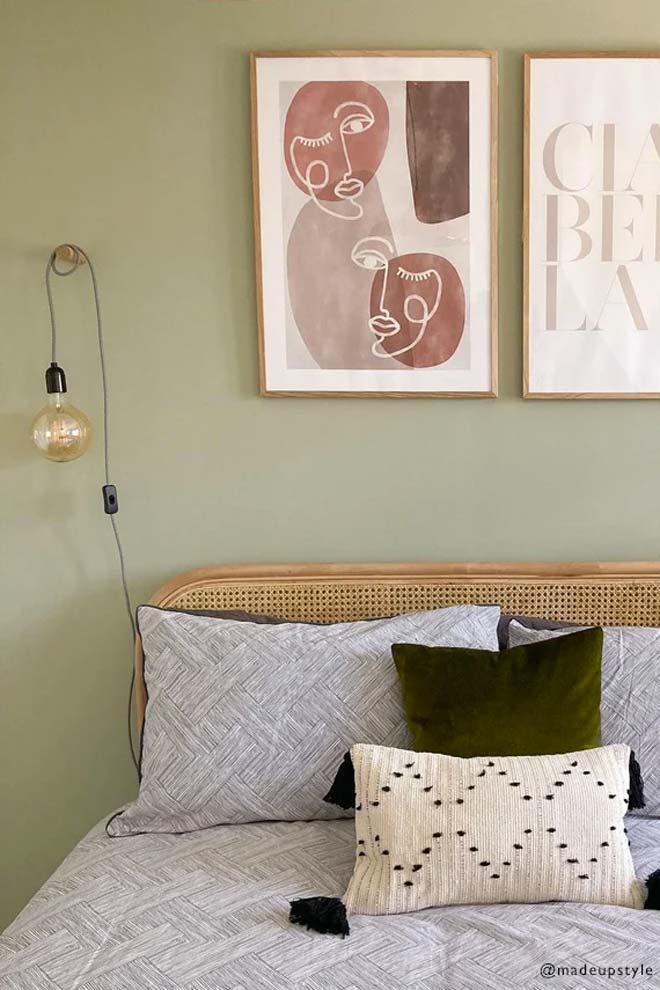 Het rotan hoofdbord en de houten lijsten staan prachtig bij de Sage green muur in deze slaapkamer.