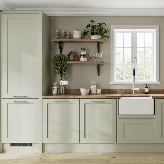 De mooie landelijke Sage green keuken van Howden, gecombineerd met een warm houten werkblad en houten wandplanken aan de muur.