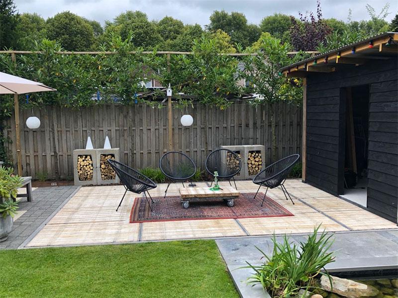 Nog een mooi voorbeeld bij handelsonderneming Bullinga van een super leuke en sfeervolle tuin met een steenschotten terras, gecombineerd met tegels en een groen gazon!