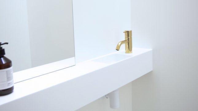 Strak en wit toilet met gouden accenten