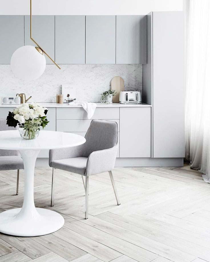 Deze strakke keuken is super chic, met lichtgrijze kasten en een wit marmer keukenblad. Klik hier voor meer foto's.