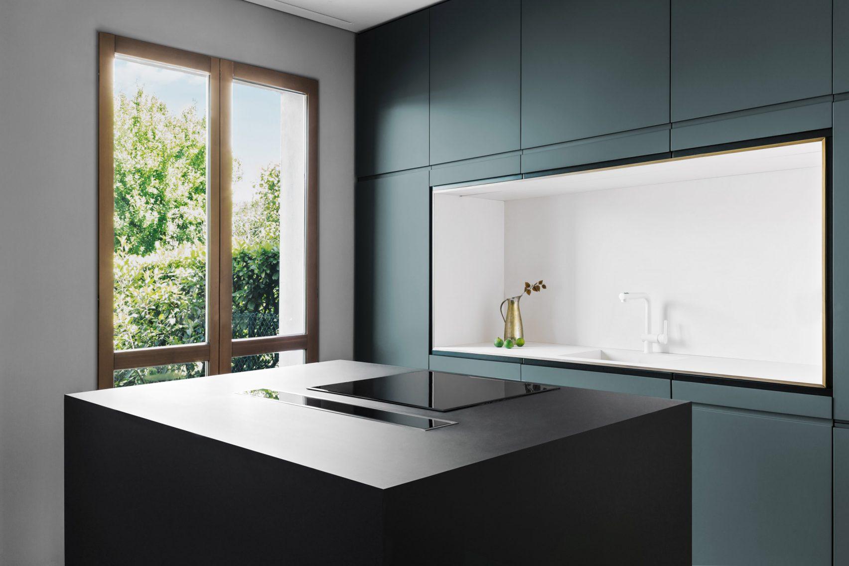 Strakke moderne keuken met blauwe wandkast en zwart kookeiland