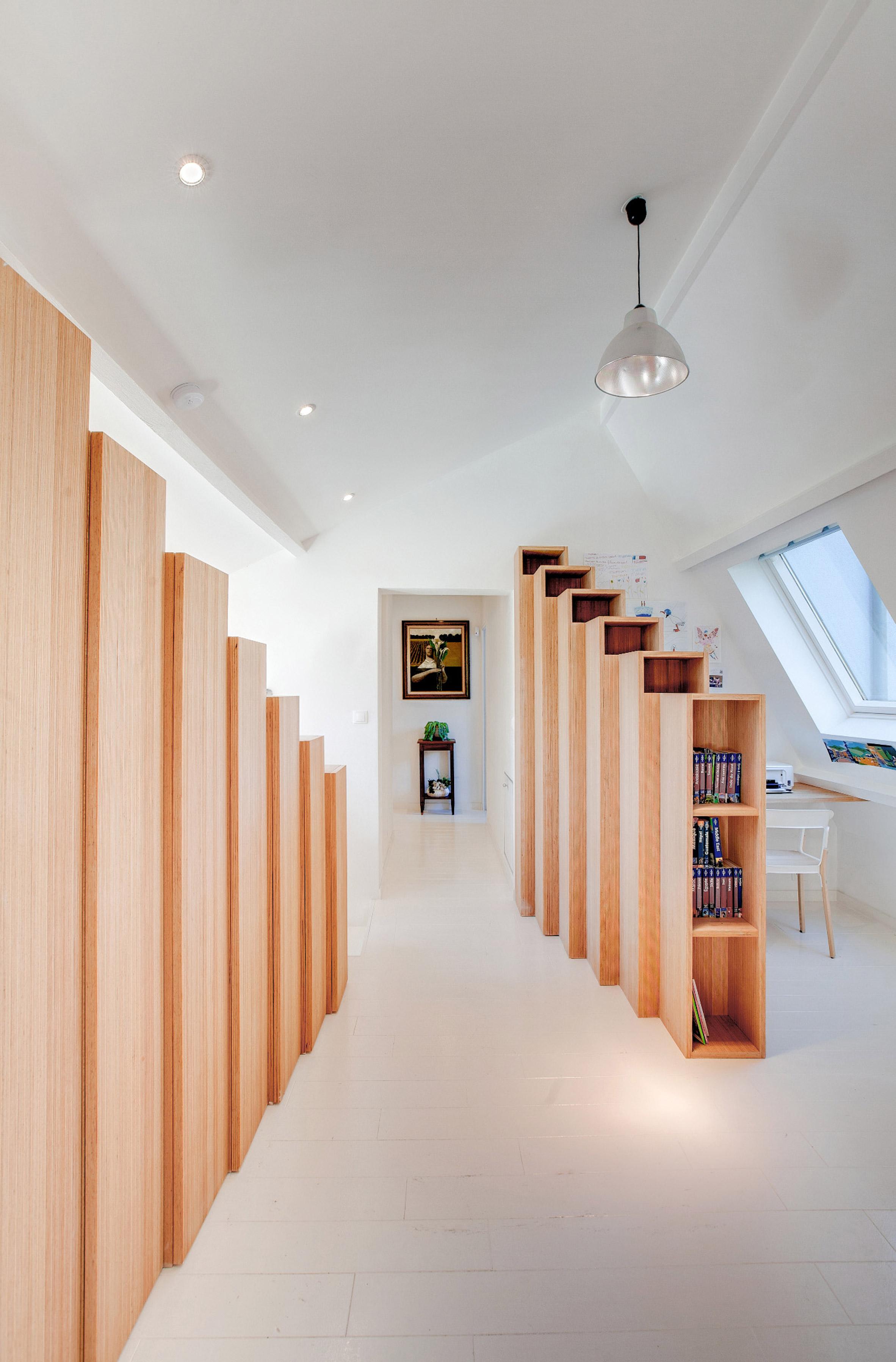 Strakke witte trap met open houten boekenkast