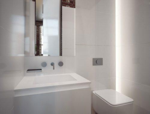 Toilet met bakstenen muur en witte wandtegels