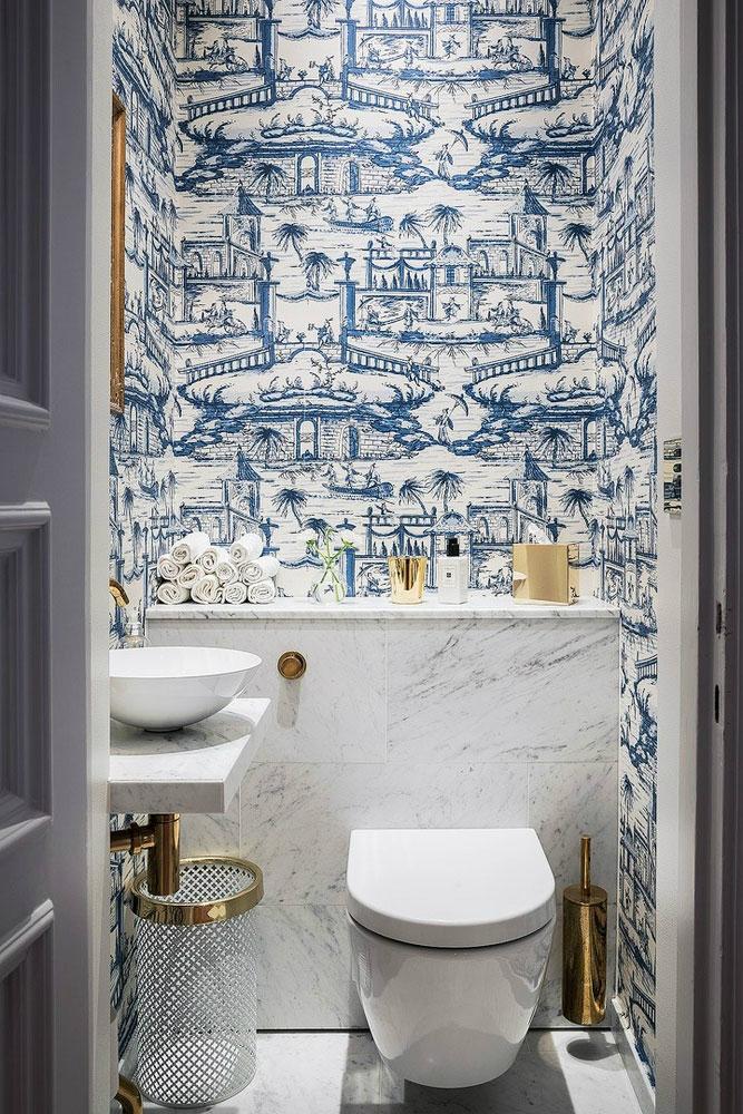 In dit toilet is er gekozen voor de combinatie van een luxe marmeren ombouw en behang.