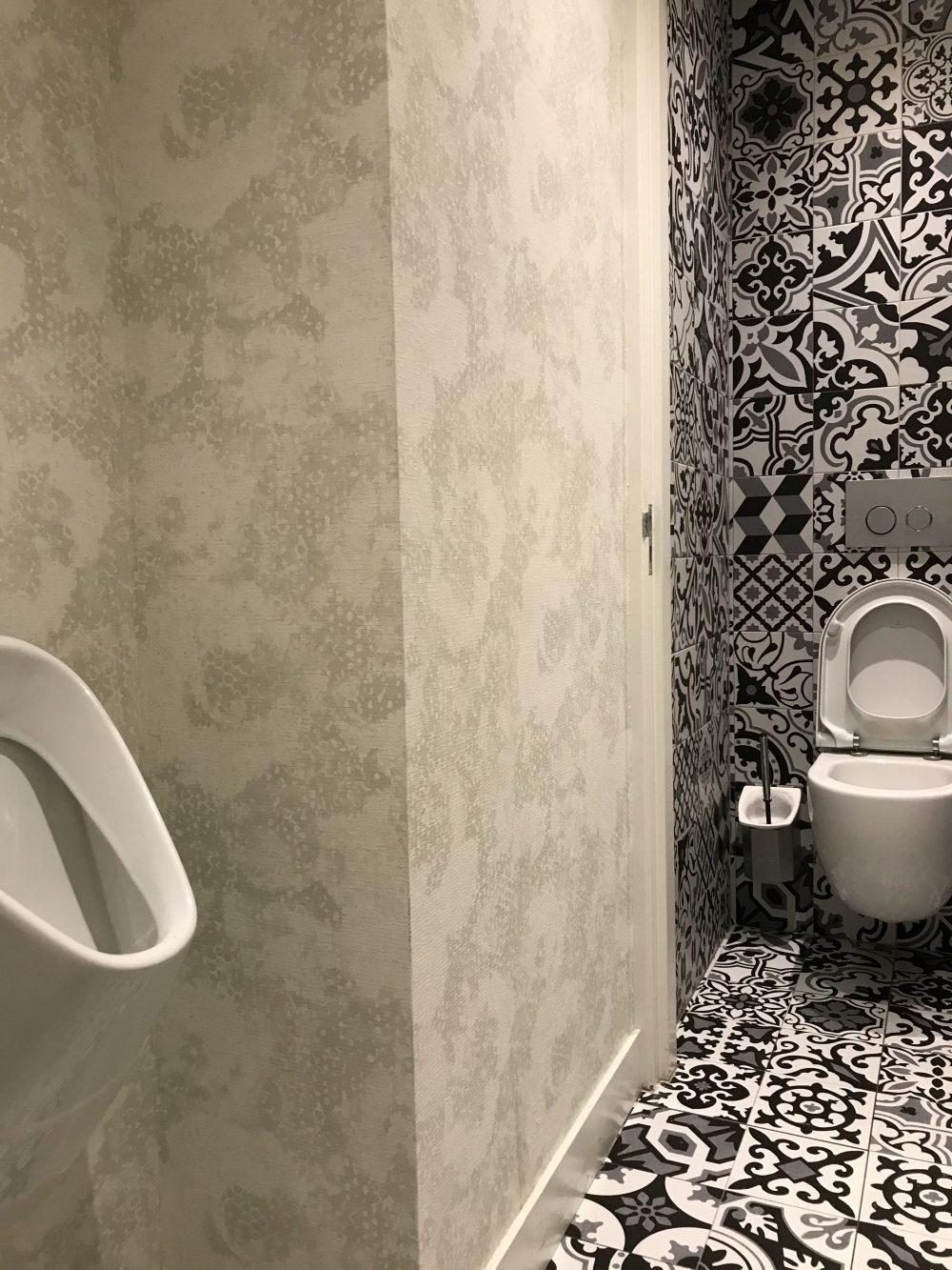 Toilet ontwerp met patchwork tegels en betonstuc