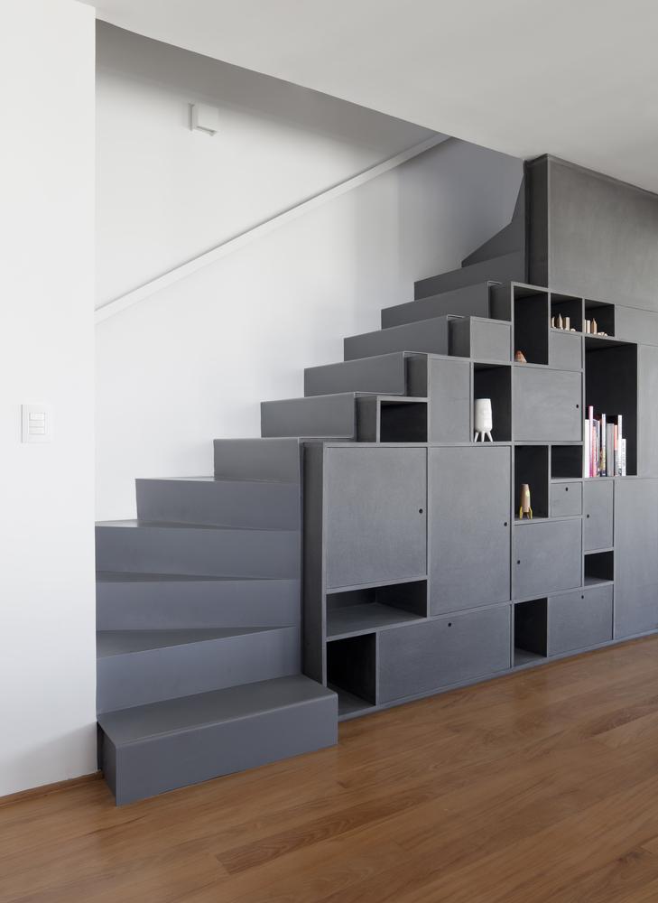 trap ideeën - moderne open trap met witte trapleuning en wandlampen en boekenkast