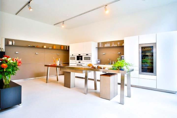 Een strakke lichte troffelvloer via Kemenade vloerafwerking in een strakke moderne keuken met eiland.