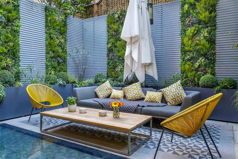 Voor deze kleine stadstuin heeft Garden builders meerdere groene plantenwanden gecreëerd op de houten schuttingen.