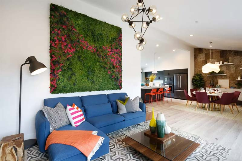 In deze ruime woonkamer is een verticale tuin gecreëerd aan de muur boven de bank.