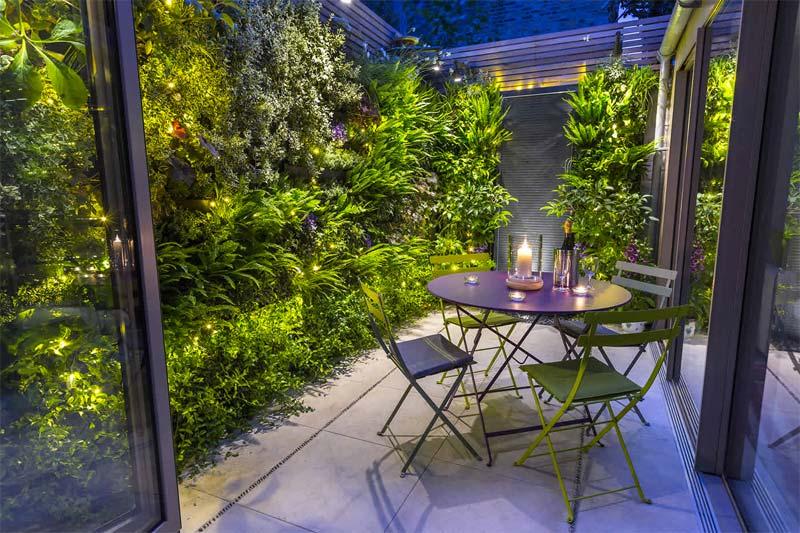 Garden builders hebben een mooie grote verticale tuin gecreëerd in deze kleine patiotuin.