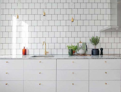 Een mooie witte keuken met een marmer keukenblad en gouden deurknoppen. Klik hier voor meer foto's.