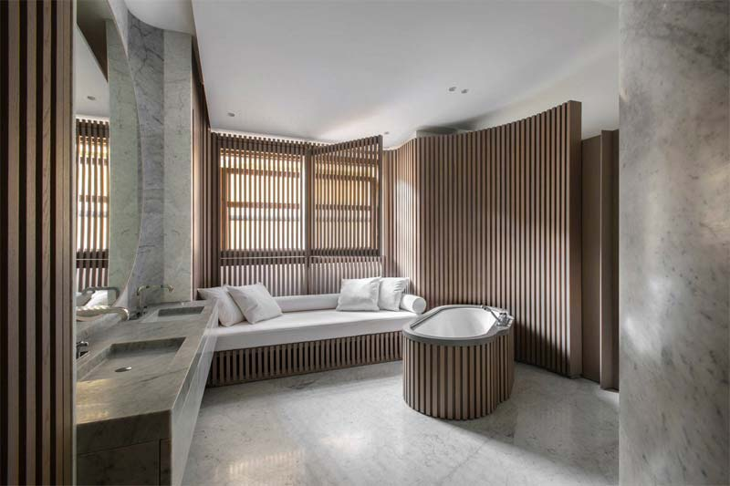 Witte marmeren tegels op de vloer en wanden combineren prachtig met de warme houten accenten in deze mooie badkamer.