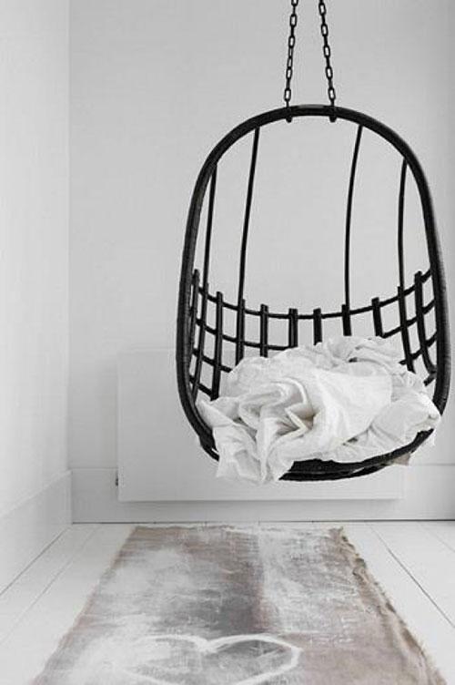 Zwarte hangstoel in een wit interieur.